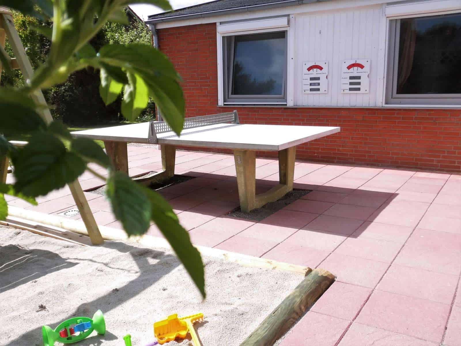 Tischtennisplatte-und-Sandkasten auf der Ostseite des Ferienhauseses mit zweiter Terrasse zum Ferienhaus Kolks Huus Besanweg 9 in Neuharlingersiel